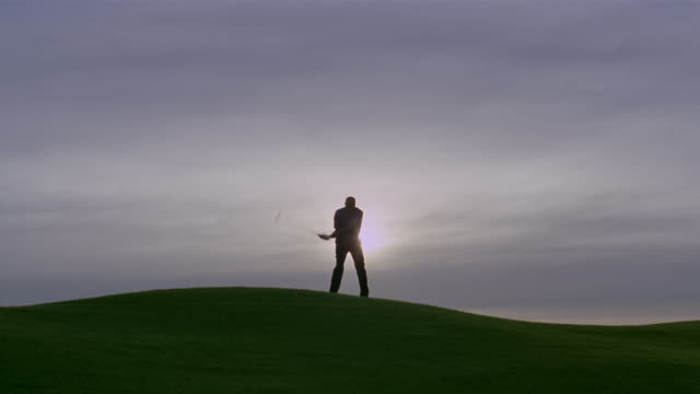 wide shot silhouette of man golfing on hill/ phoenix, arizona - only mature men stock videos & royalty-free footage