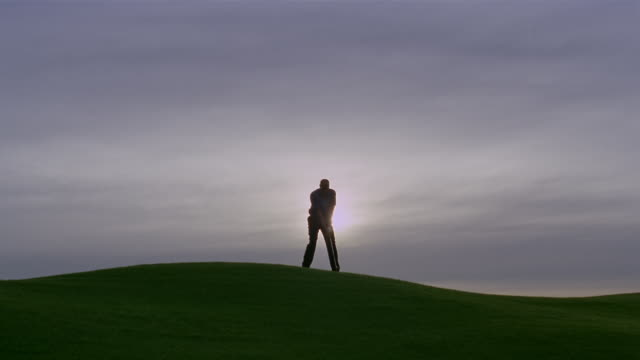 vidéos et rushes de wide shot silhouette of man golfing on hill/ phoenix, arizona - parcours de golf