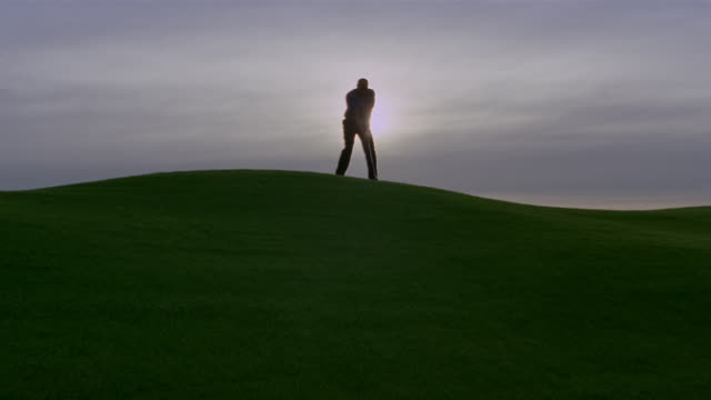 wide shot silhouette of man golfing on hill/ phoenix, arizona - golf swing silhouette stock videos & royalty-free footage