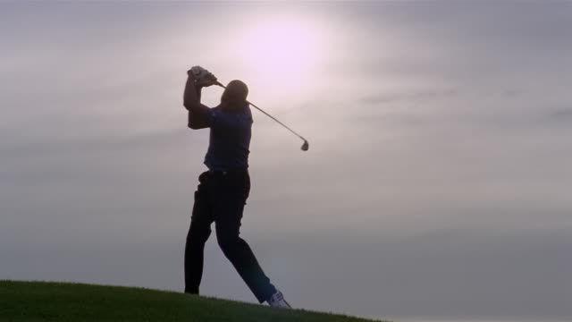 wide shot silhouette of man golfing on hill/ phoenix, arizona - ゴルフクラブ点の映像素材/bロール