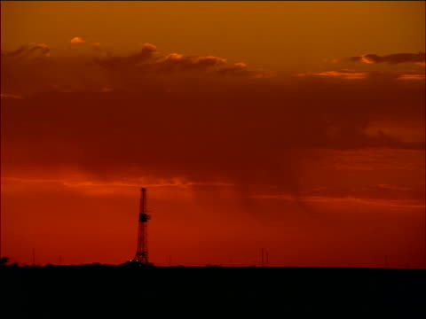 wide shot silhouette of oil derrick with clouds above on texas plain at sunset / orange filter - 1996 stock videos & royalty-free footage