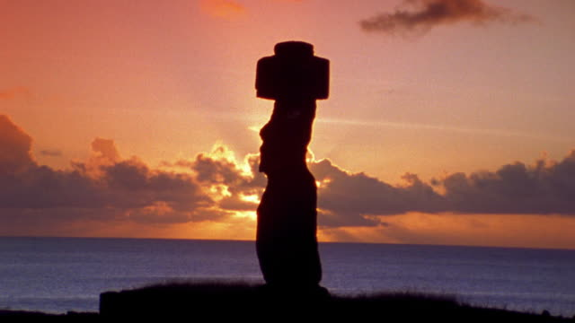 wide shot silhouette of stone moai statue on easter island with sunset + pacific ocean in background / south pacific - south pacific ocean stock videos and b-roll footage