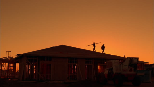 Wide shot silhouette of two construction workers carrying plank on roof /  Phoenix, Arizona