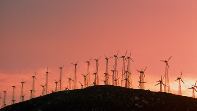 wide shot silhouette wind turbines spinning on hill at sunset / tehachapi pass, california - turbine stock-videos und b-roll-filmmaterial