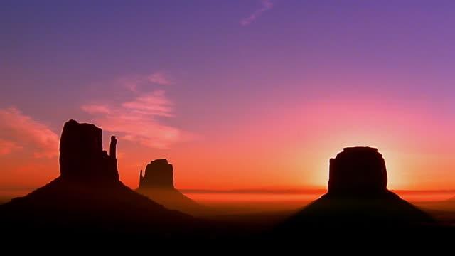 wide shot silhouetted buttes in momument valley at sunset or sunrise - dramatisk himmel bildbanksvideor och videomaterial från bakom kulisserna