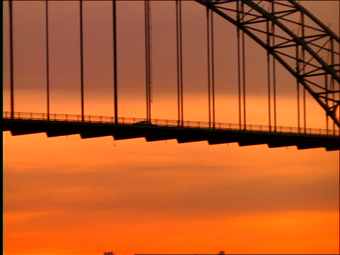 wide shot pan silhouetted car driving on bridge at sunset / yaquina bay, newport, oregon - yaquina bay lighthouse stock videos & royalty-free footage