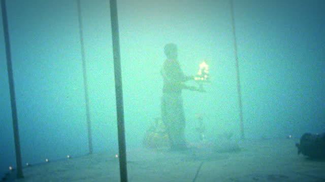 vídeos de stock e filmes b-roll de wide shot silhouetted man swinging torch around in fog / varanasi, india - super exposto
