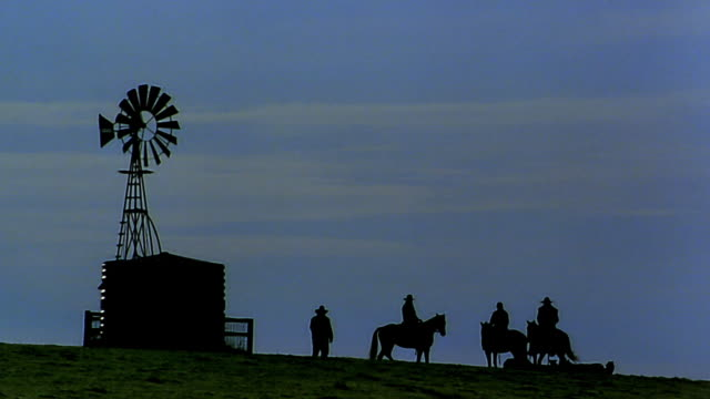 wide shot silhouetted ranch hands on horseback at dusk - ranch stock videos & royalty-free footage
