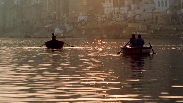 Wide shot silhouetted three people in rowboats on Ganges River with city in background / Varanasi, India