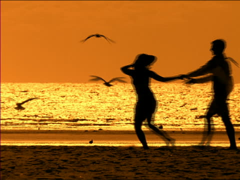 wide shot silhouettes of couple on beach with man picking woman up and spinning her at dusk / miami, florida - paar mittleren alters stock-videos und b-roll-filmmaterial