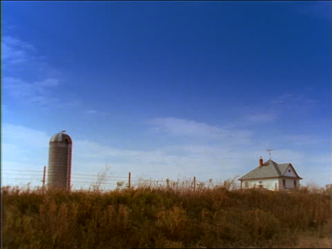 wide shot silo + farmhouse in golden field / southern minnesota - cinematography stock videos & royalty-free footage