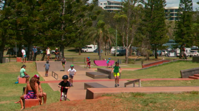 wide shot skate park at Town Beach Park Port Macquarie various anonymous kids mostly on razer scooters / pan skate park woman sits reading under...