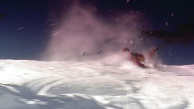 fast motion wide shot skier with poles tops crest of hill, somersaults, stands on one leg and falls near tree - falla av bildbanksvideor och videomaterial från bakom kulisserna