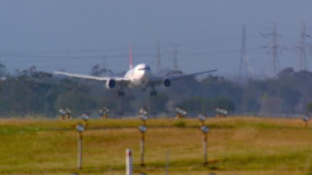 wide shot slow motion commercial jet landing w/heat waves rippling - landefahrwerk stock-videos und b-roll-filmmaterial