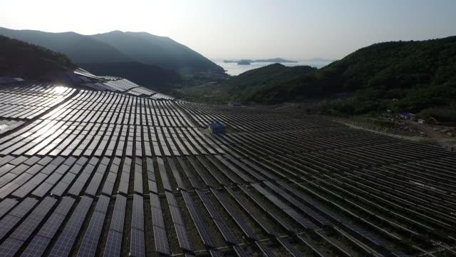 wide shot slow r l track, slow backward track, slow upward track above solar power plant - stromnetz stock-videos und b-roll-filmmaterial