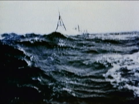 vidéos et rushes de 1989 wide shot small cargo ship being thrown around on huge waves in very rough sea - bercement