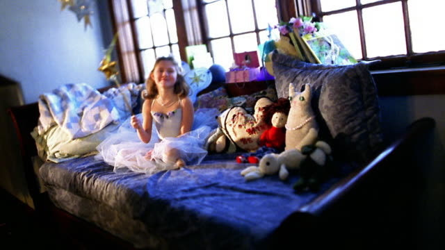 Wide shot small girl in princess outfit with magic wand sitting on bed with stuffed animals
