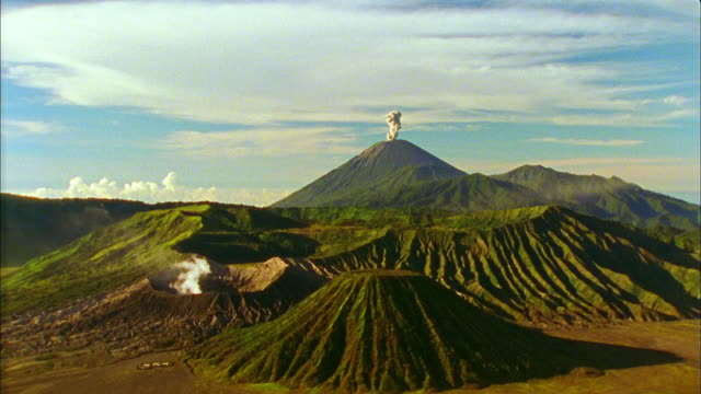 wide shot smoke rising from mount semeru with bromo craters in foreground / java, indonesia - mount semeru stock videos & royalty-free footage