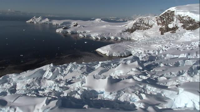 wide shot snowcapped glaciers floating on coast of antarctic sea/ antarctica - antarctica aerial stock videos & royalty-free footage