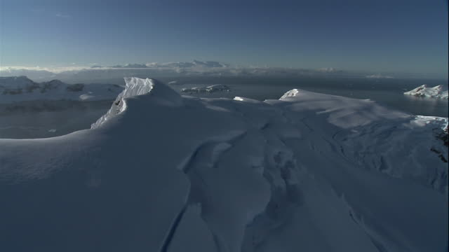 vídeos de stock, filmes e b-roll de wide shot snowcapped glaciers floating on coast of antarctic sea/ antarctica - pólo sul