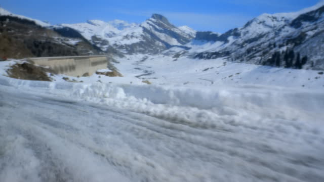 vídeos de stock, filmes e b-roll de wide shot snow-covered road winding through french alps/ france - forma da água