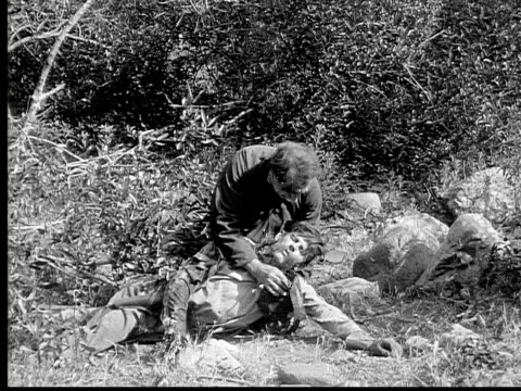 1913 reenactment b/w wide shot soldier helping wounded man and giving him water from canteen during civil war battle reenactment / usa  - 1913 stock-videos und b-roll-filmmaterial