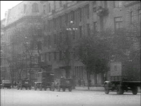 B/W 1956 wide shot PAN Soviet tanks trucks in city square / Hungarian uprising