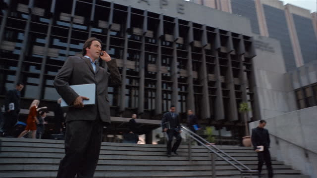 Wide shot spinning point of view businessman talking on cell phone and holding laptop in front of office building