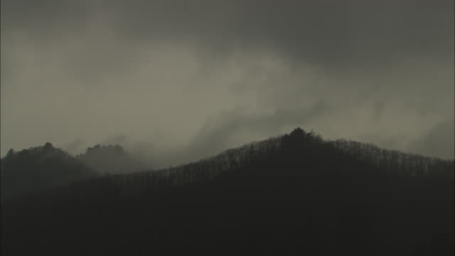 wide shot static _ dark clouds pass over a mountain during a rainstorm / ya'an, china - mountain range stock videos & royalty-free footage