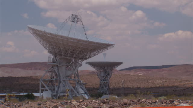 Wide Shot static _ Shadows crawl over two radio telescope dishes / Fort Irwin, California, USA