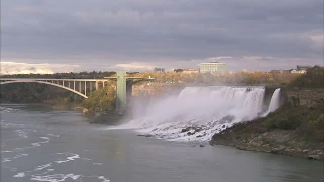 wide shot static - a bridge crosses the water near the niagara falls / ontario, canada - river niagara stock videos & royalty-free footage