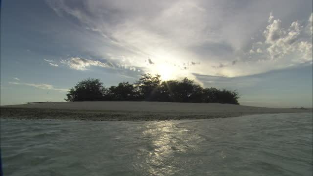 Wide Shot static - A brilliant sun glows above an island / Great Barrier Reef, Australia