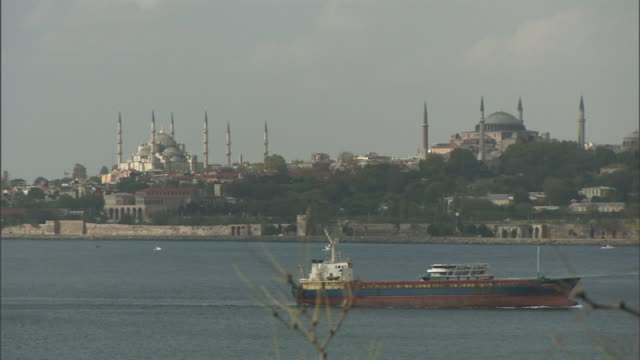 wide shot static - a cargo ship and a ferry boat glide through the harbor near hagia sophia and the blue mosque. / istanbul, turkey - golden horn istanbul stock videos and b-roll footage