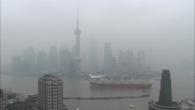 wide shot static - a cargo ship sails past haze shrouded skyscrapers in downtown beijing./beijing, china - smog stock videos & royalty-free footage