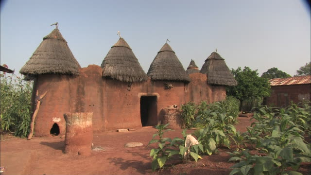 wide shot static - a doorway leads into a hut with four thatched roofs. / benin - adobe stock videos & royalty-free footage