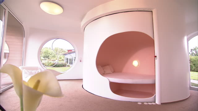 Wide Shot static - A futuristic room and bathroom rotate at the center of a larger living room. / Germany