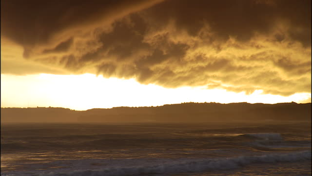 wide shot static , a golden sunset illuminates the clouds and ocean waves. / puerto rico - seascape stock videos & royalty-free footage