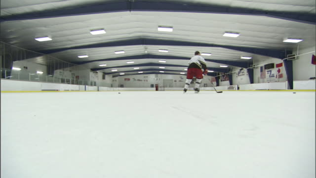 Wide Shot static - A hockey player practices in a rink. / North Carolina, USA