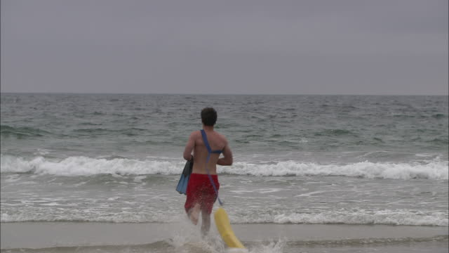wide shot static - a lifeguard charges into the ocean - drowning stock videos and b-roll footage