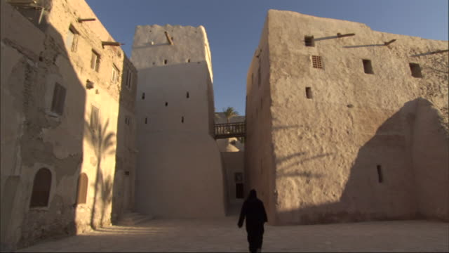 wide shot, static - a monk walks between the adobe buildings of a monastery / egypt - adobe bildbanksvideor och videomaterial från bakom kulisserna