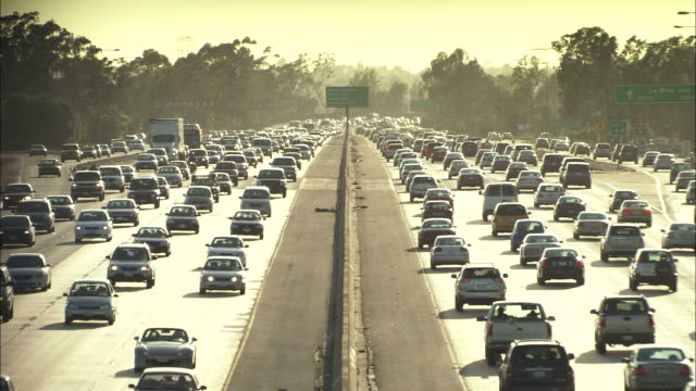 wide shot static - a steady stream of heavy traffic moves in opposite directions/hawaii, usa - pollution stock videos & royalty-free footage
