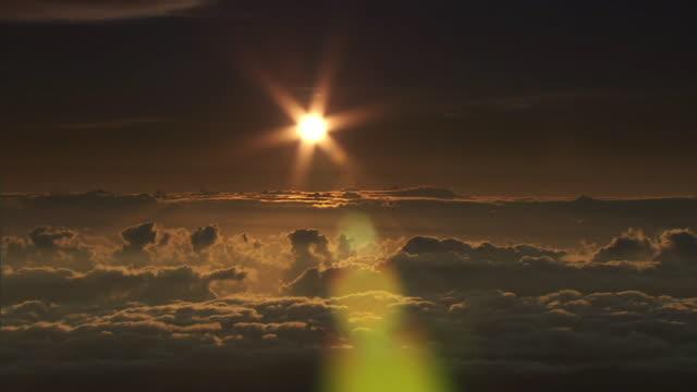 wide shot static - a sunburst shines over a sea of clouds at mauna kea, hawaii. / mauna kea, hawaii, usa - ハワイ島点の映像素材/bロール