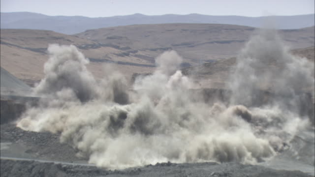 wide shot static - an explosion erupts from barren land, sending up smoke and dust clouds. / south africa - miniera video stock e b–roll