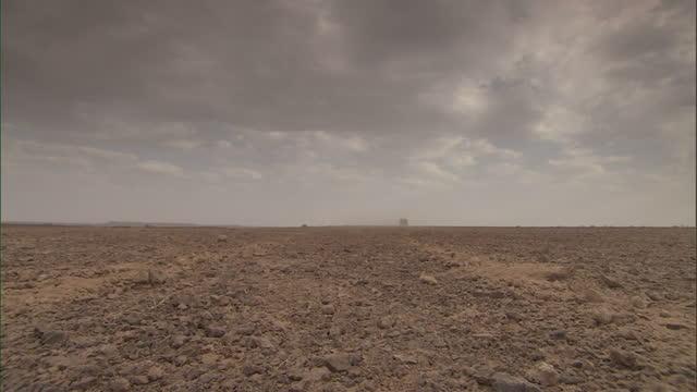 vídeos y material grabado en eventos de stock de wide shot static - an suv drives across a vast, flat desert / sahara, egypt - suv