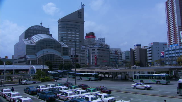 Wide Shot static - Buses pull into Shinagawa train station in Hamamatsu city, Japan. / Hamamatsu city, Japan
