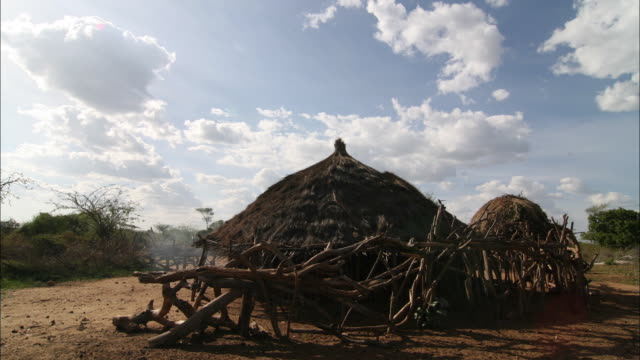 wide shot static - cumulus clouds drift over a grass hut in benin. / benin - grass hut stock videos & royalty-free footage
