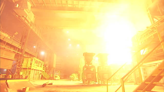 wide shot static - huge billowing flames cast an orange glow throughout a steel mill / claymont, delaware  - stahlwerk stock-videos und b-roll-filmmaterial