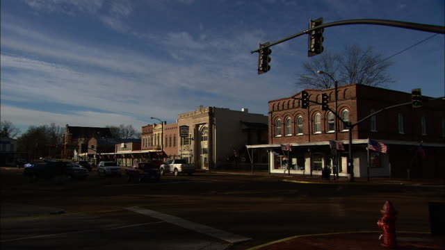 wide shot static - light traffic moves through a small-town intersection. / mississippi, usa - piccola cittadina video stock e b–roll