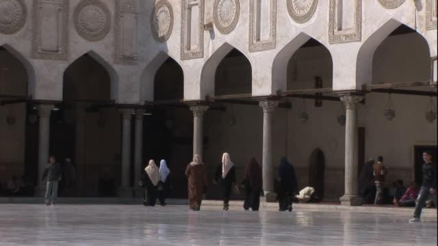 wide shot, static - pedestrians walk across a plaza / egypt - burka stock videos and b-roll footage