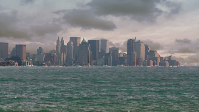 wide shot static - rising floodwater nearly reaches the top of the new york city skyline in a computer-generated animation. / new york city, new york, usa - überschwemmung stock-videos und b-roll-filmmaterial